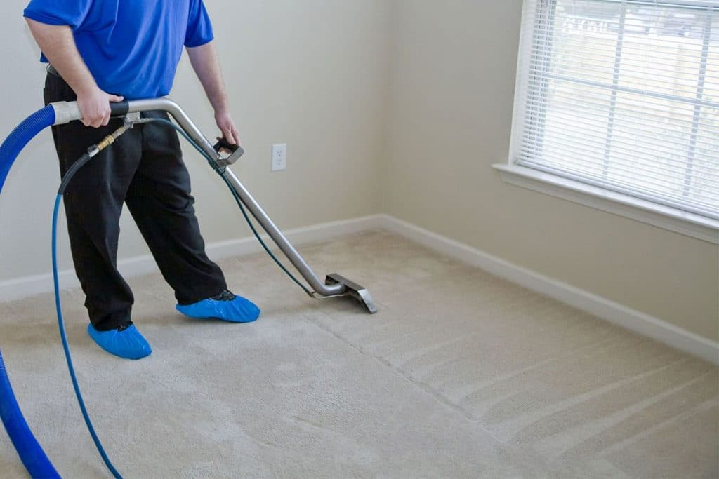 QDC Employee cleaning carpet with commercial cleaning equipment