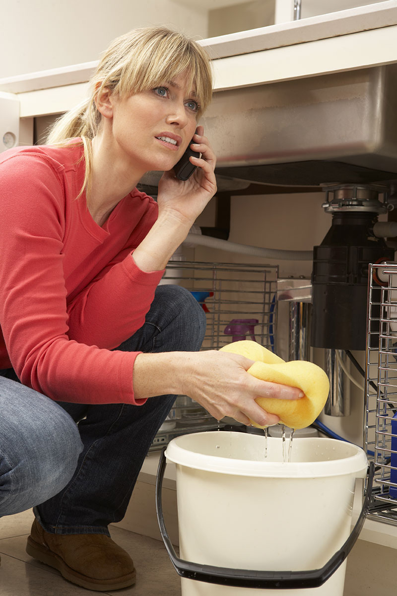 Woman Mopping Up Leaking Sink On Phone To Emergency Disaster Cleanup Company