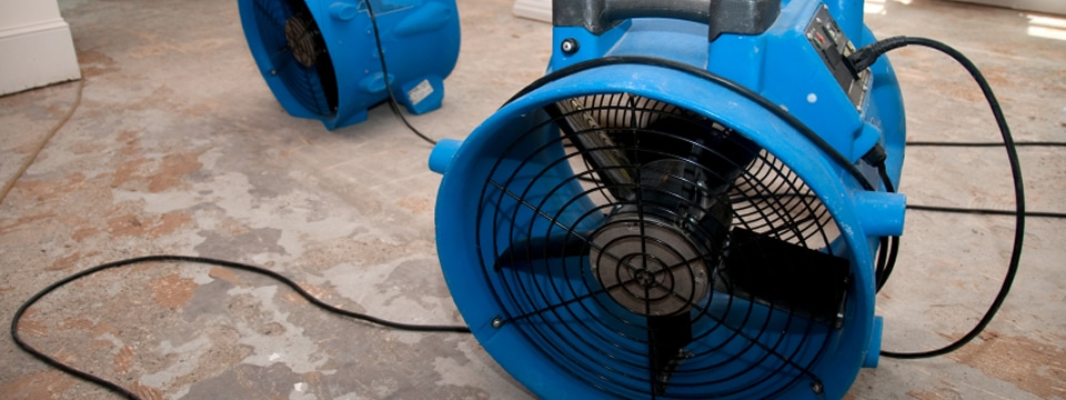 Fans blow drying a floor with water and flood damage.